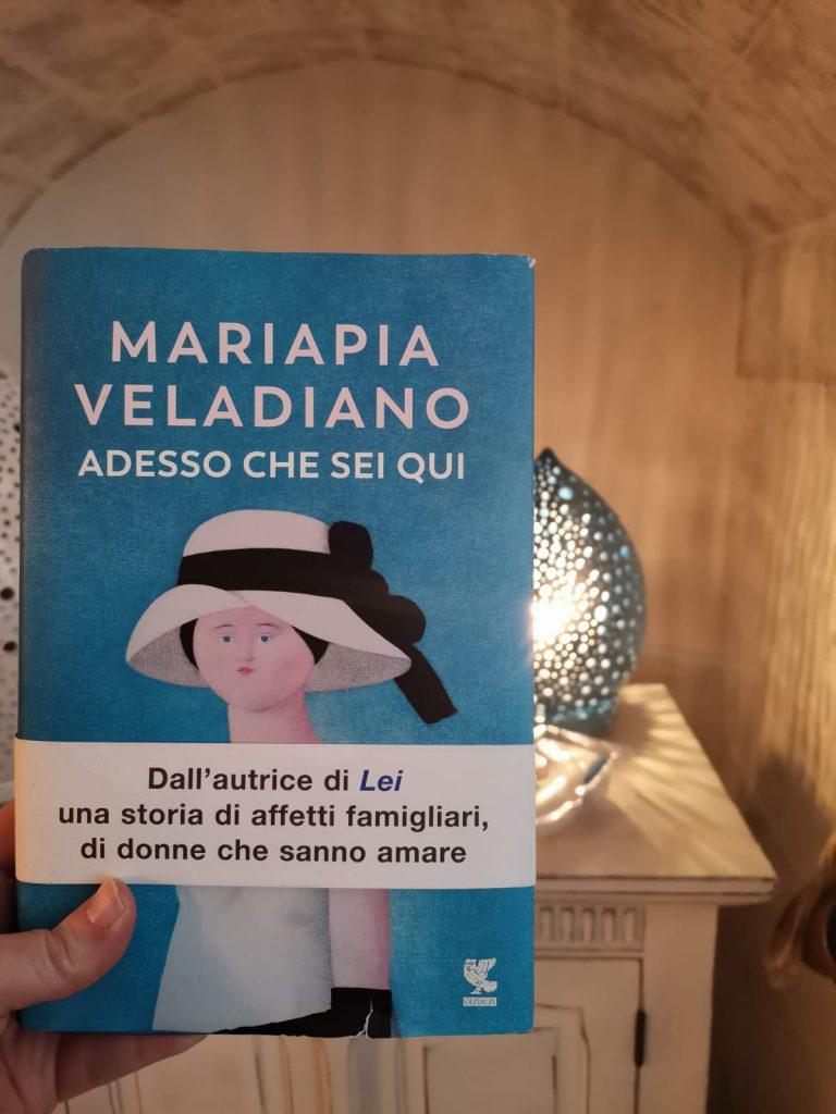 Adesso che sei qui - Mariapia Veladiano - romanzo con copertina azzurra. Sullo sfondo una lampada a forma di pomo pugliese di porcellana dello stesso colore