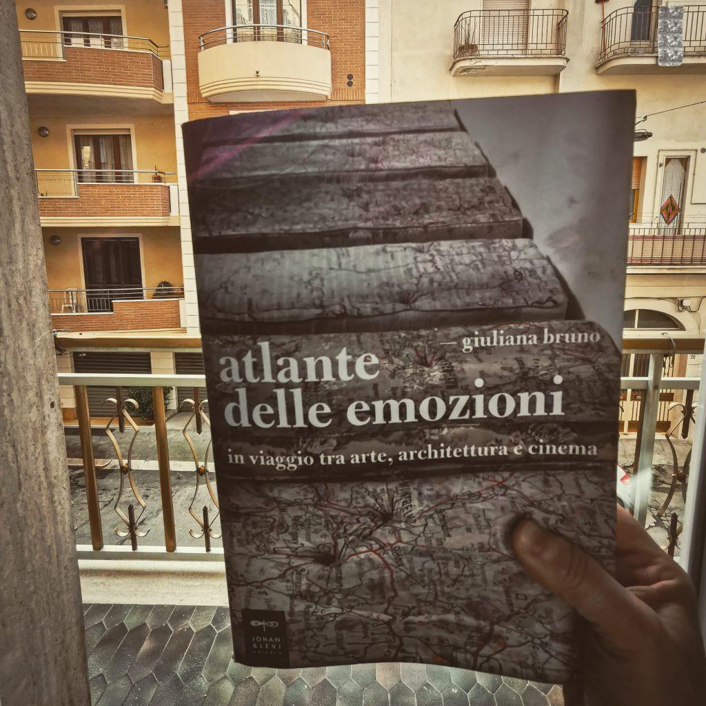 Atlante delle emozioni di Giuliana Bruno: libro in primo piano sorretto da una mano su sfondo di paese