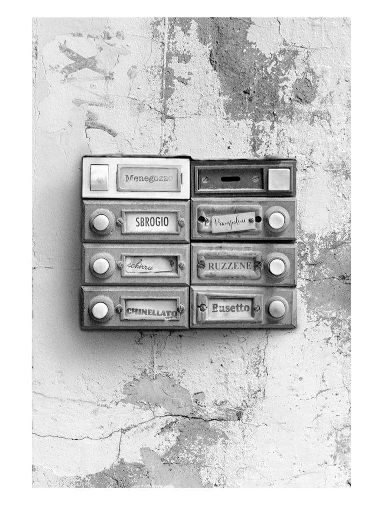 Il citofono con l'elenco dei nomi dei condomini: le sette famiglie del romanzo. Muro pieno di crepe. Foto con cui si apre il romanzo