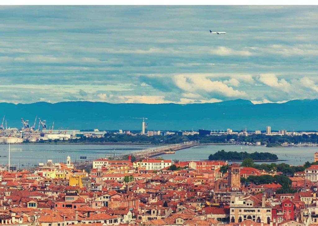 Panorama di Mestre: schiera di case dai tetti spioventi e, in fondo, porto Marghera
