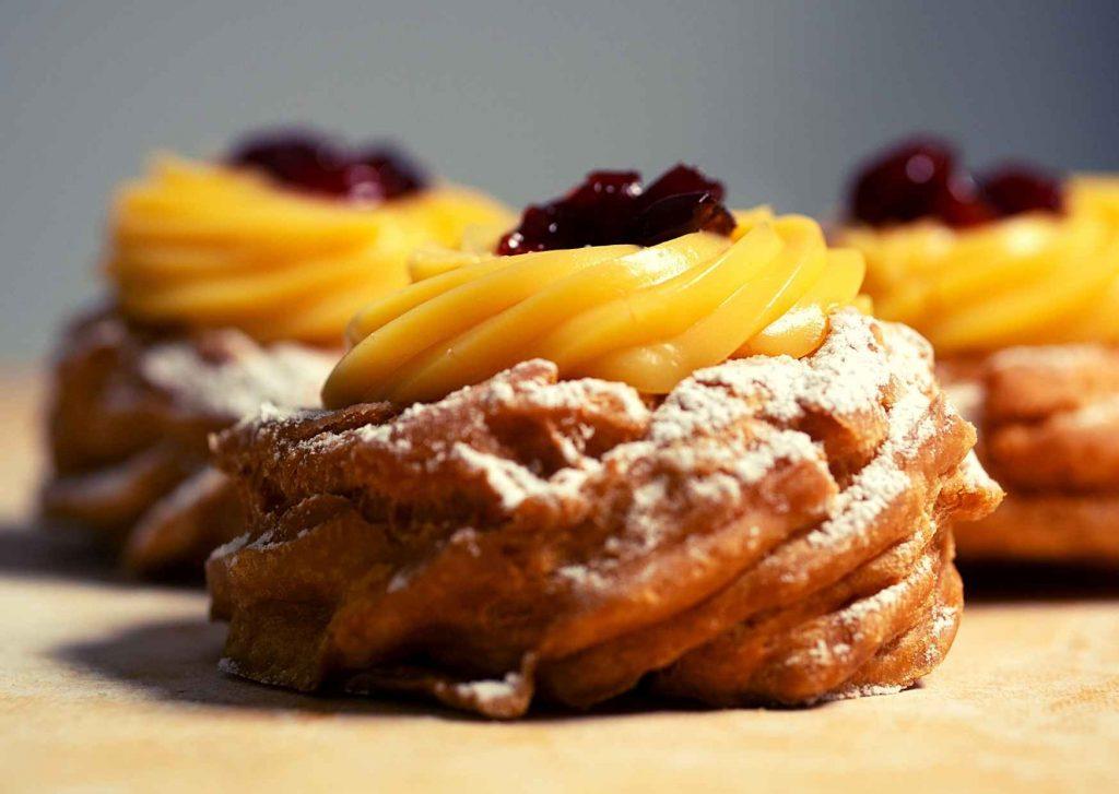 zeppole in primo piano: anelli fritti dolci farciti con crema e amarena