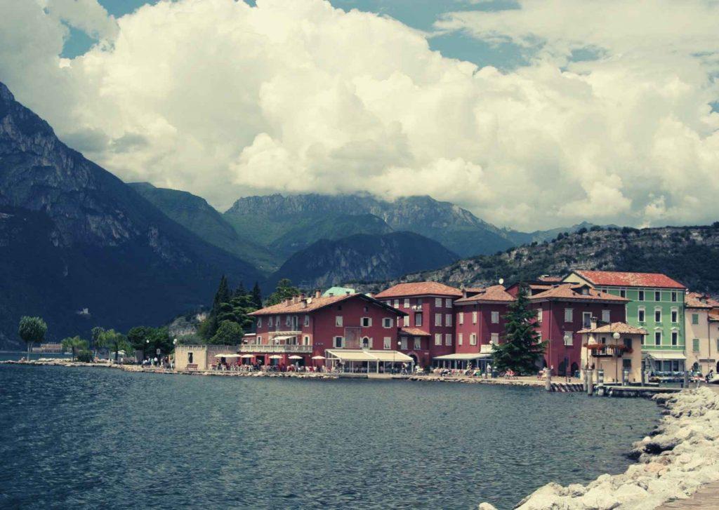 Lago di Garda con case colorate sulla riva e alte montagne del Trentino alle spalle. Cielo nuvoloso.