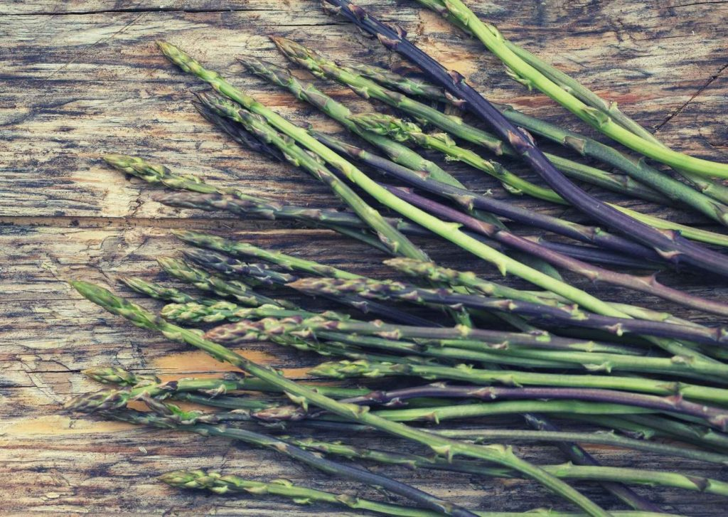 Asparagi selvatici in primo piano su tavolaccio di legno