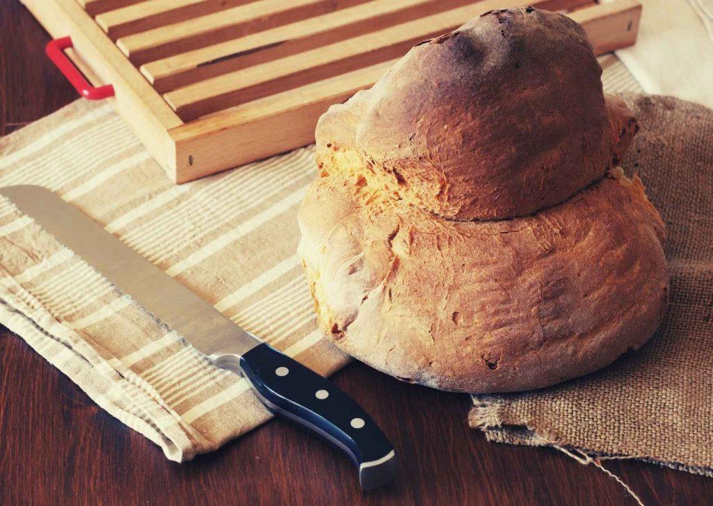Pane di Altamura DOP nella sua forma tipica adagiato su sacchi e tovagliette e accompagnato dal coltello per affettarlo