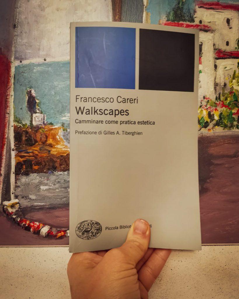 Walkscapes: libro in primo piano fra quadri che raffigurano paesaggi