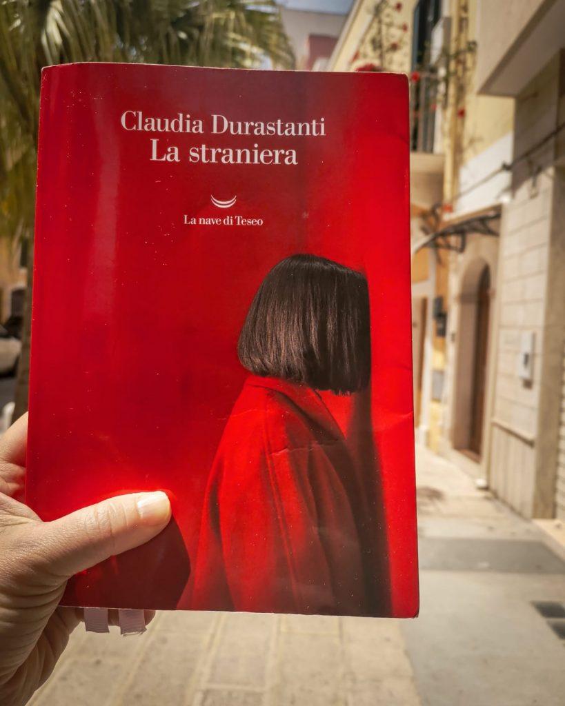 La straniera - Claudia Durasanti: copertina del romanzo rosso scarlatto e strada con antiche case e palma sullo sfondo