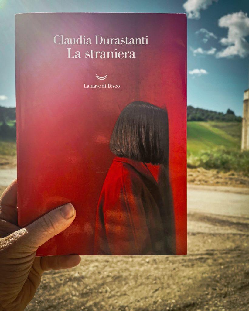 La straniera - Claudia Durasanti: copertina del romanzo rosso scarlatto e collina verde sullo sfondo