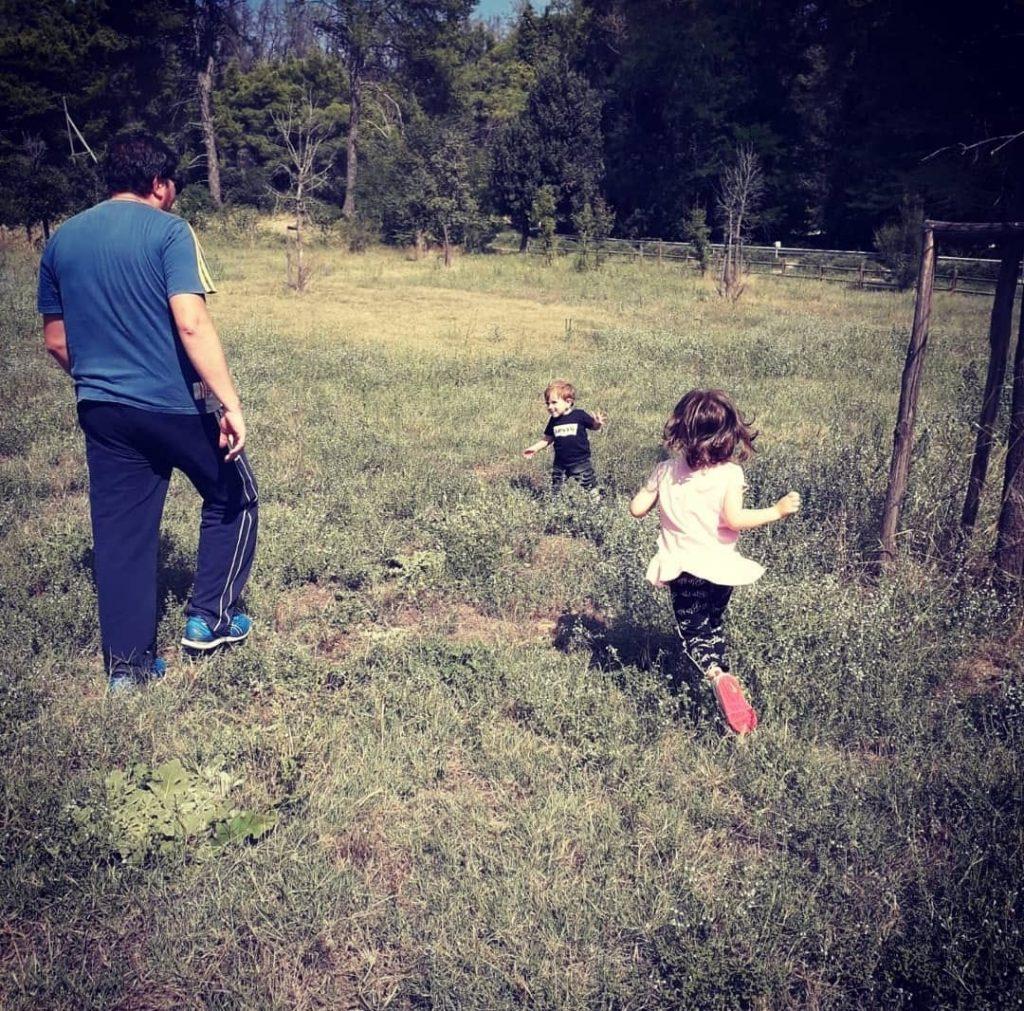 Picnic in Puglia: bambini che corrono col papà tra cespugli. Bosco in lontananza