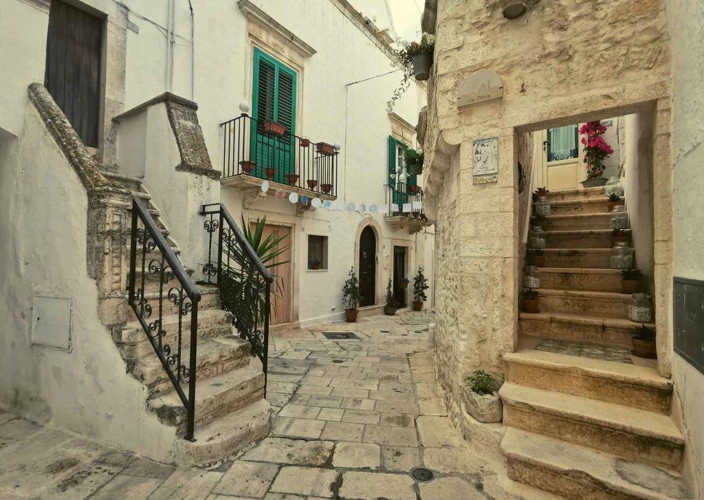 vicolo di Locorotondo: strada basolata con scalette esterne di accesso alle case, ringhiere di ferro battuto, persiane, vasi decorativi