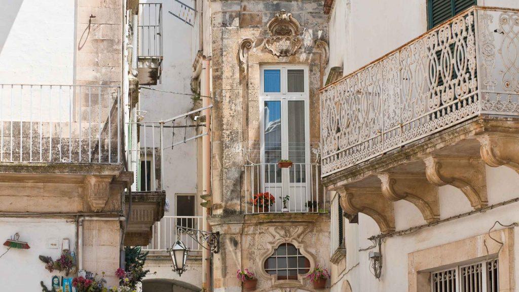Martina Franca: balconi con ringhiere in ferro battuto, finestre con fiori, lampioni, case addossate fra loro