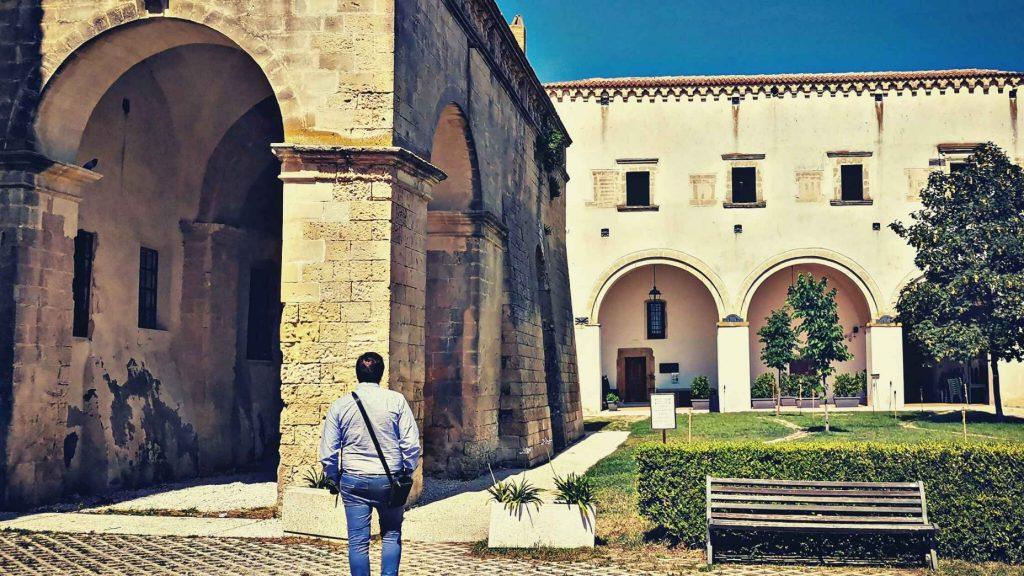 Montescaglioso: chiostro di abbazia Panchina, archi, siepi, piccoli alberi