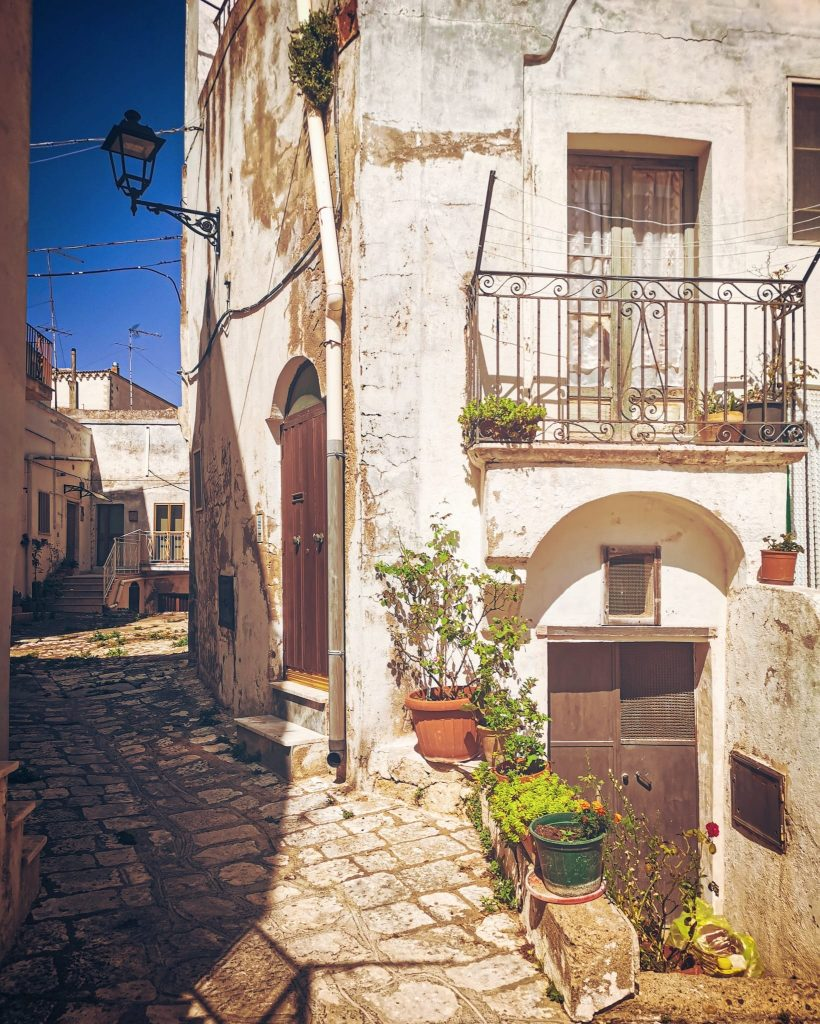 vicolo basolato con antiche case, vasi si fiori disordinati, balconcino con finestra e tendine, muri scrostati, lampione e altre case sul fondo