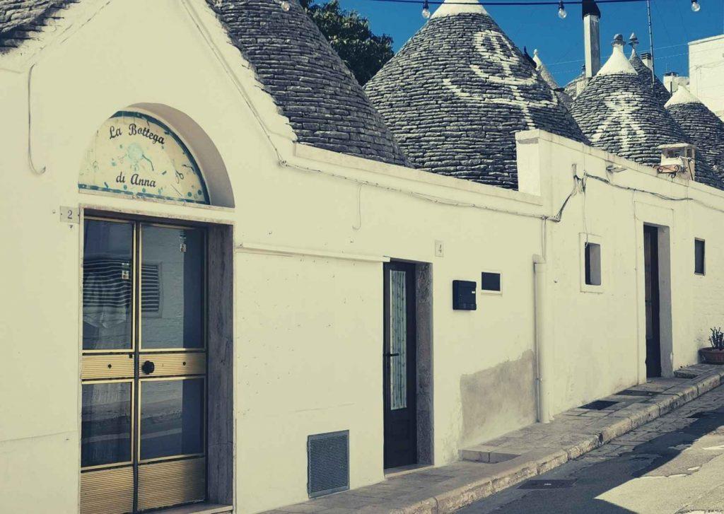 Trulli: porte, tetti con pinnacoli e simboli, strada in salita