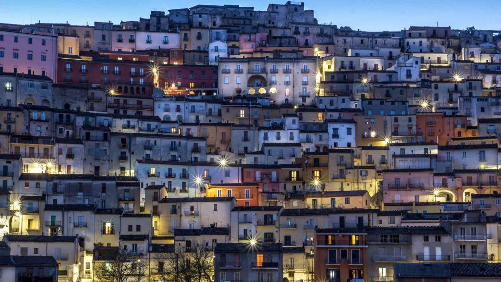 Avellino centro storico illuminato nella prima sera, case a ventaglio lungo la collina con tetti spioventi e facciate di colori diversi