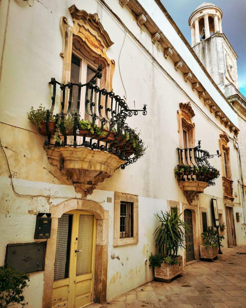 Locorotondo: strada basolata, balconi in stile barocco con ringhiere arcuate e tante piante