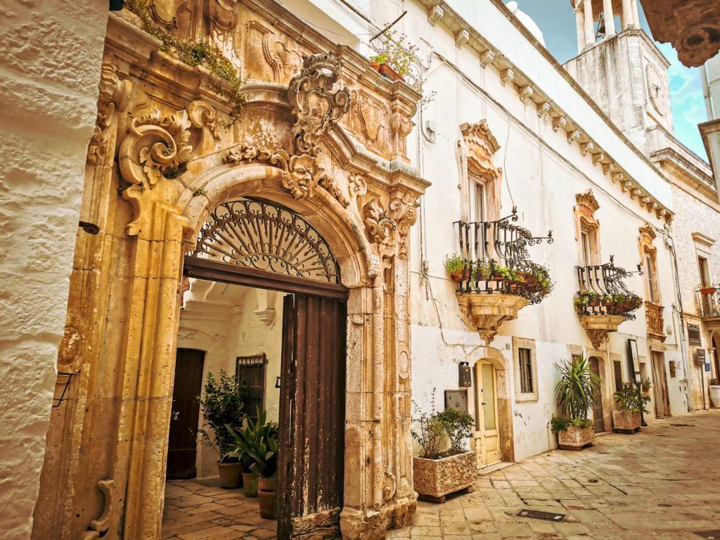 Palazzo Morelli con grande portone decorato in primo piano. Fra le decorazioni: racemi e mascheroni.