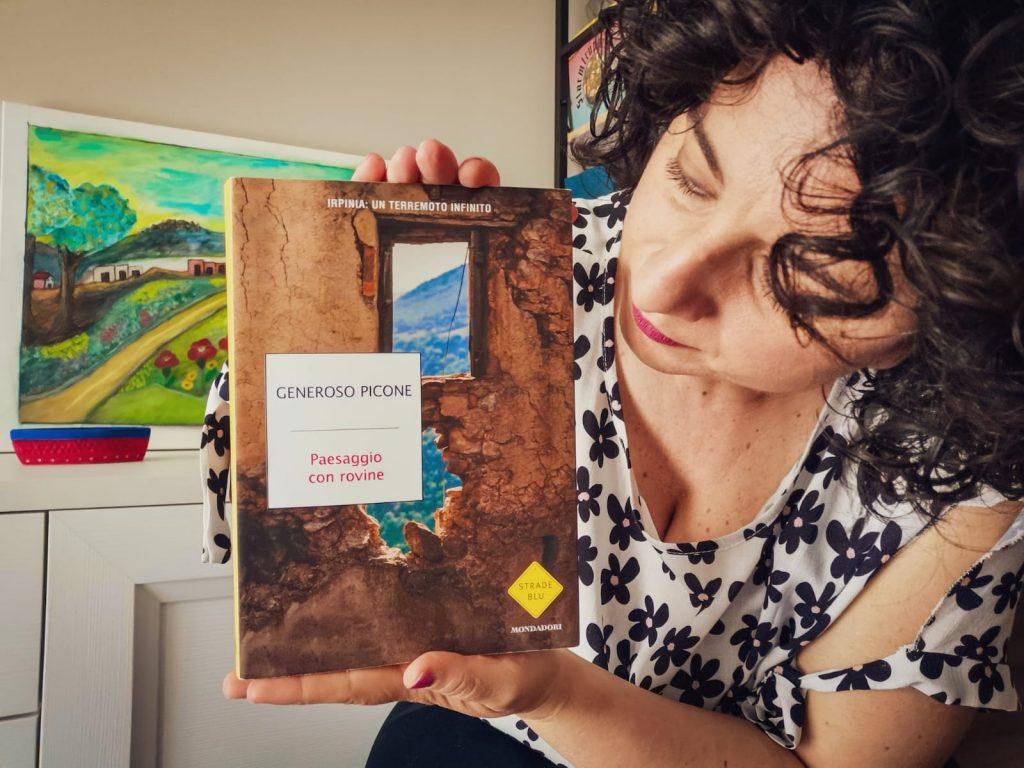 Lettrice mostra il saggio Paesaggio con rovine. Sullo sfondo una consolle con quadro di paesaggio sul ripiano