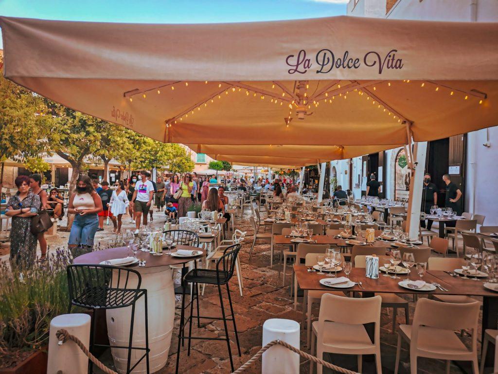 5 ristoranti di pesce a Monopoli: la Dolce Vita. Tavolini all'aperto davanti a una piazzetta alberata. Lucine a decorare i tendoni.