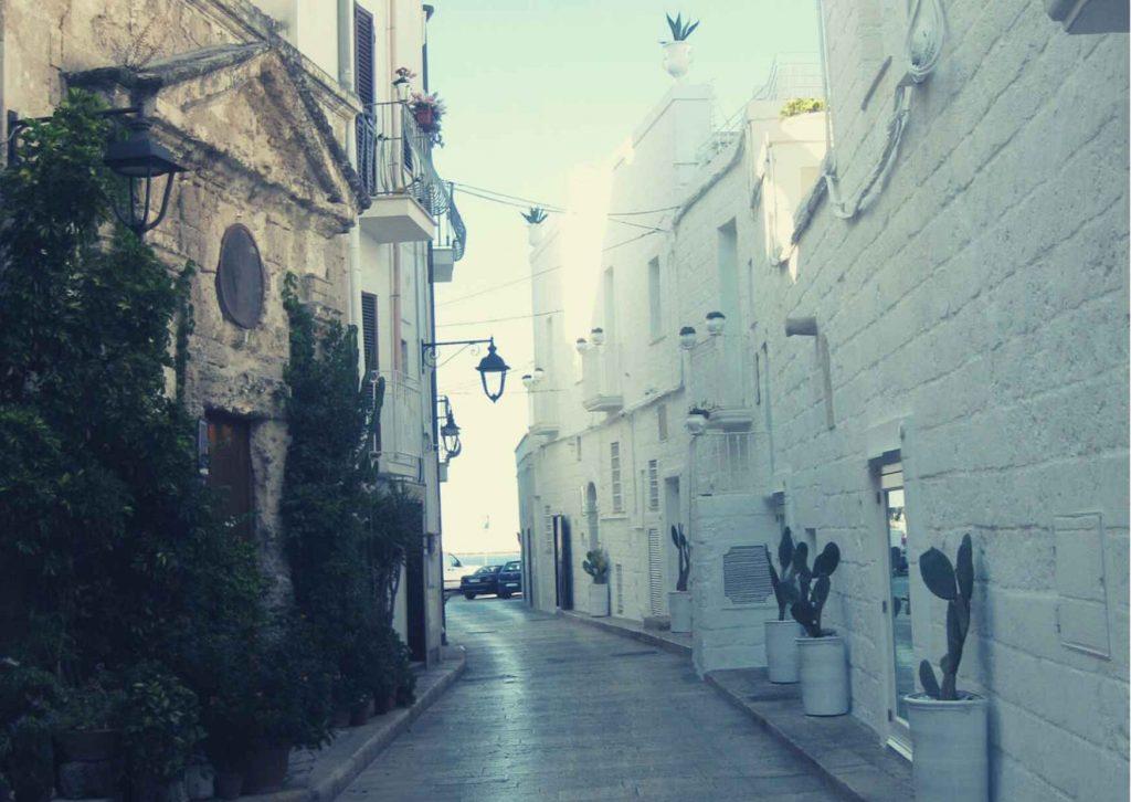 Chiesetta con piante rampicanti; di fronte muraglia bianca con ingresso al ristorante decorato con pale di fichidindia. balconcini bianchi con vasi decorativi di ceramica, strada che va verso il mare