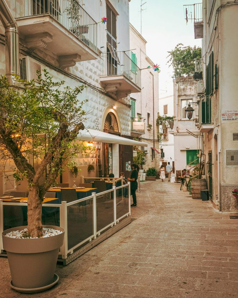 5 ristoranti di pesce a Monopoli: il Guazzetto. Ingresso con tavolini all'esterno. Strada con tipiche persiane verdi e molte piante decorative