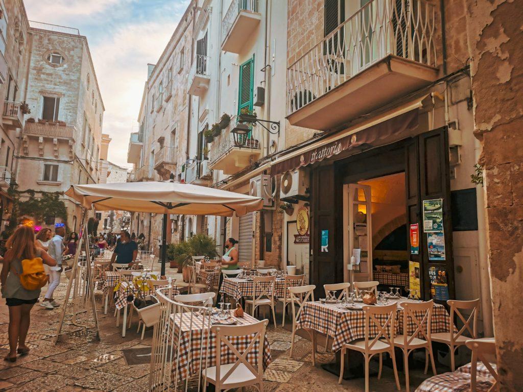5 ristoranti a Monopoli: La locanda dei mercanti. Tavolini all'aperto con tovagliato a quadri, ingresso e scorcio della via affollata e piena di abitazioni caratteristiche