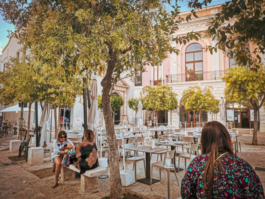 piazza Garibaldi con alberelli tutt'intorno e tavolini al centro. Sul fondo i grandi finestroni ottocenteschi della biblioteca. Donne sedute sulle panchine.