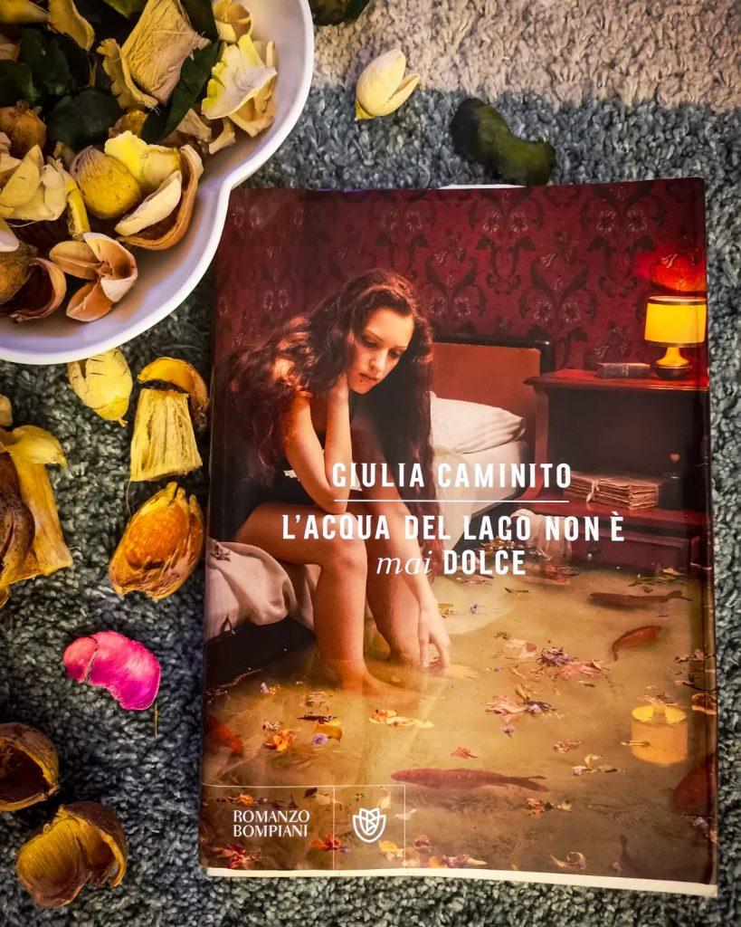 L'acqua del lago non è mai dolce - Giulia Caminito: copertina con figura femminile seduta sul letto e acque stagnanti di lago ai piedi che inondano la stanzetta illuminata dall'aba-jour, carta da parati rosso scuro