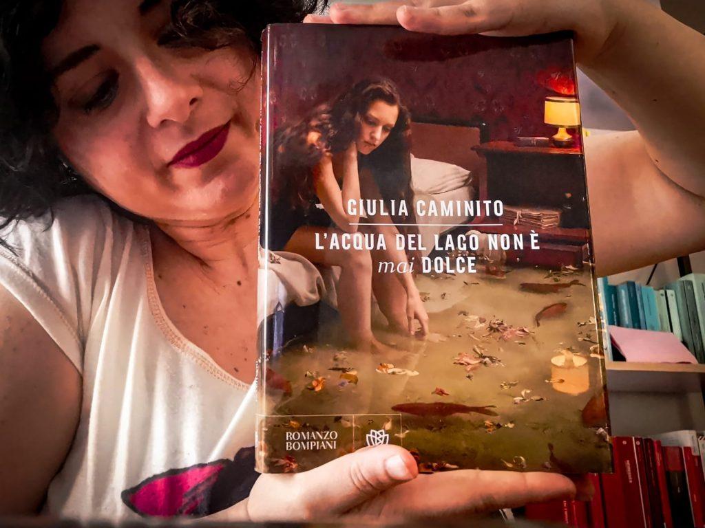 Libro con copertina in primo piano. Il libro è sorretto fra le mani di una donna riccia. Alle spalle scaffali con libri colorati