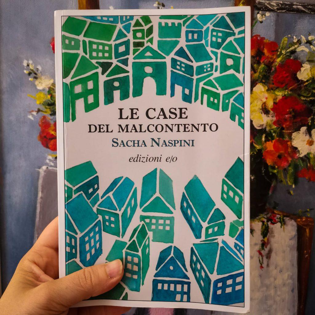 Le case del malcontento - Sacha Naspini: copertina con molte casette verde-azzurre. Sullo sfondo un quadro che raffigura dei fiori su una vecchia seggiola