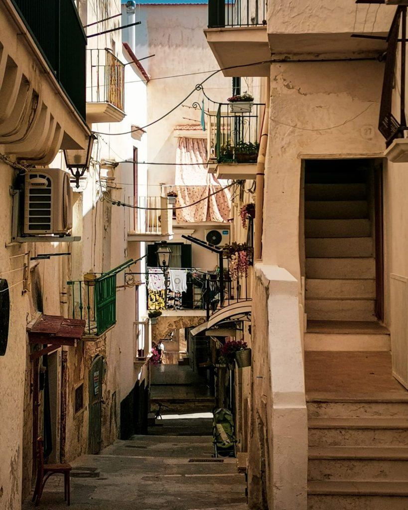 Vieste Vecchia: particolare di un vicolo con molti balconcini, panni stesi e tende fiorite, una sedia davanti al portoncino, un passeggino