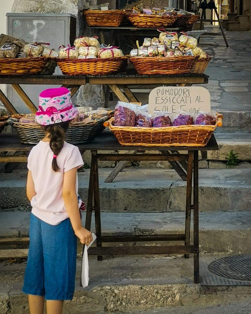 Vieste con bambini: bancarella con prodotti tipici e cartelli scritti a mano, una bambina sta guardando dei pomodori secchi in esposizione