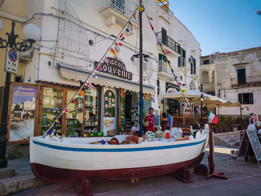 Barca piena di souvenir davanti a un negozietto pieno di calamite e ceramiche