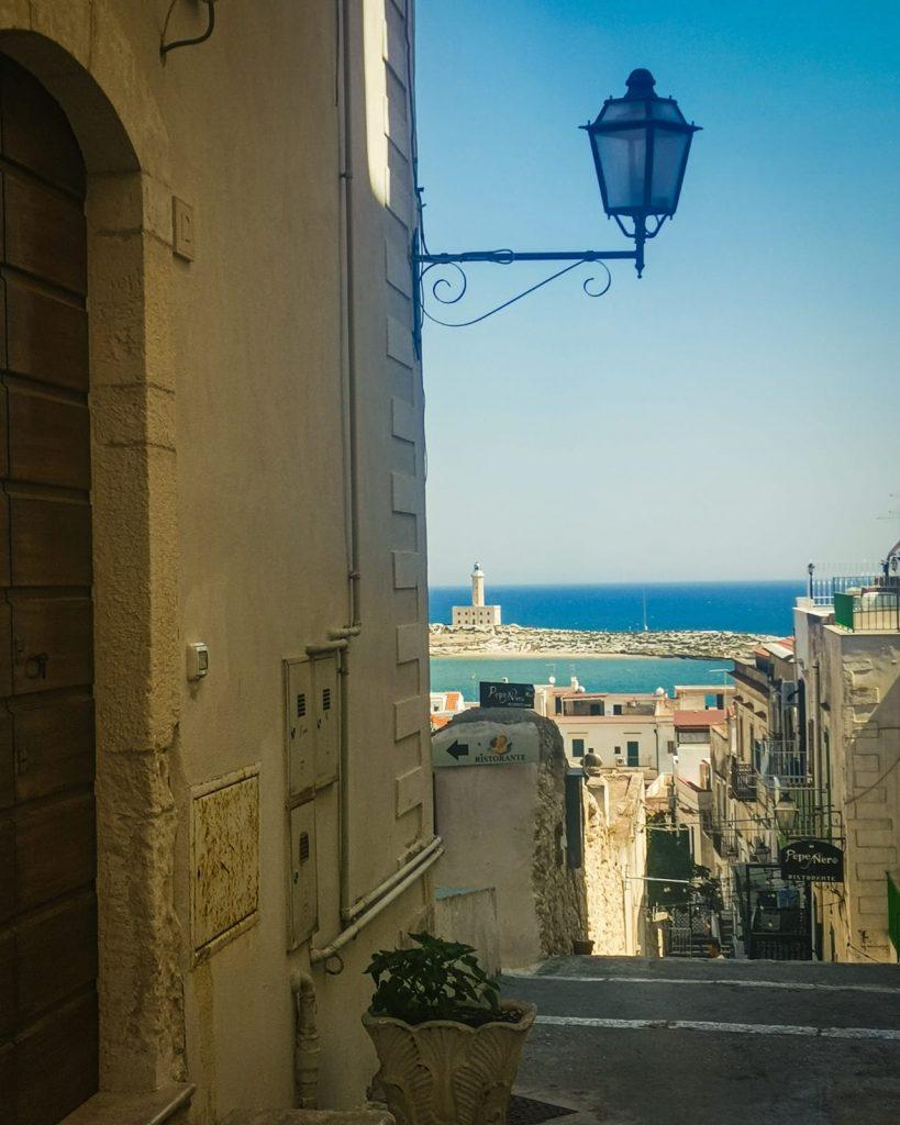 Vieste Vecchia: panorama dall'alto con lampione e case. Faro in lontananza su mare turchese