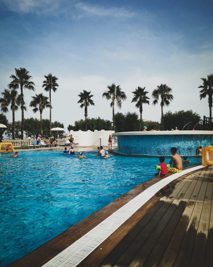 Vieste con bambini: la piscina del residence con la vasca principale, le palme tutt'intorno e la vasca idromassaggio sopraelevata. Bambini che nuotano