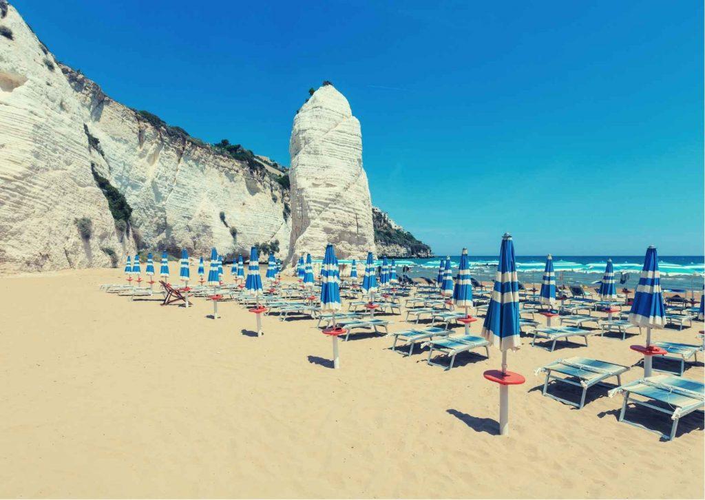spiaggia di Pizzomunno con monolite bianco e scogliera, ombrelloni chiusi sulla spiaggia, mare sul fondo sotto un cielo senza nuvole