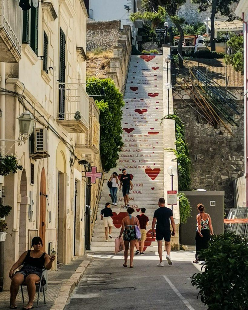 Vieste: la scalinata dell'Amore. Scala dipinta di bianco e piena di cuori rossi. Vi sale e vi scende molta gente, soprattutto coppie. Alberi in cima.