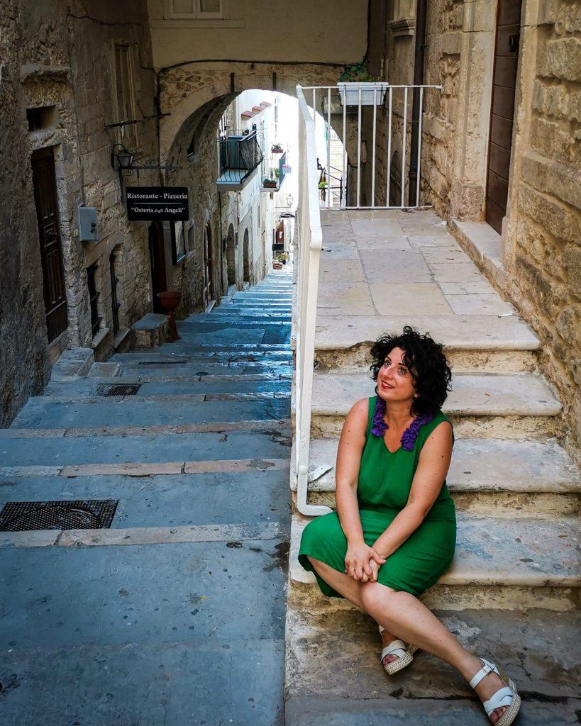 Anna seduta su una scaletta della Vieste Vecchia, in lontananza un arco, l'insegna di un'osteria. Case.