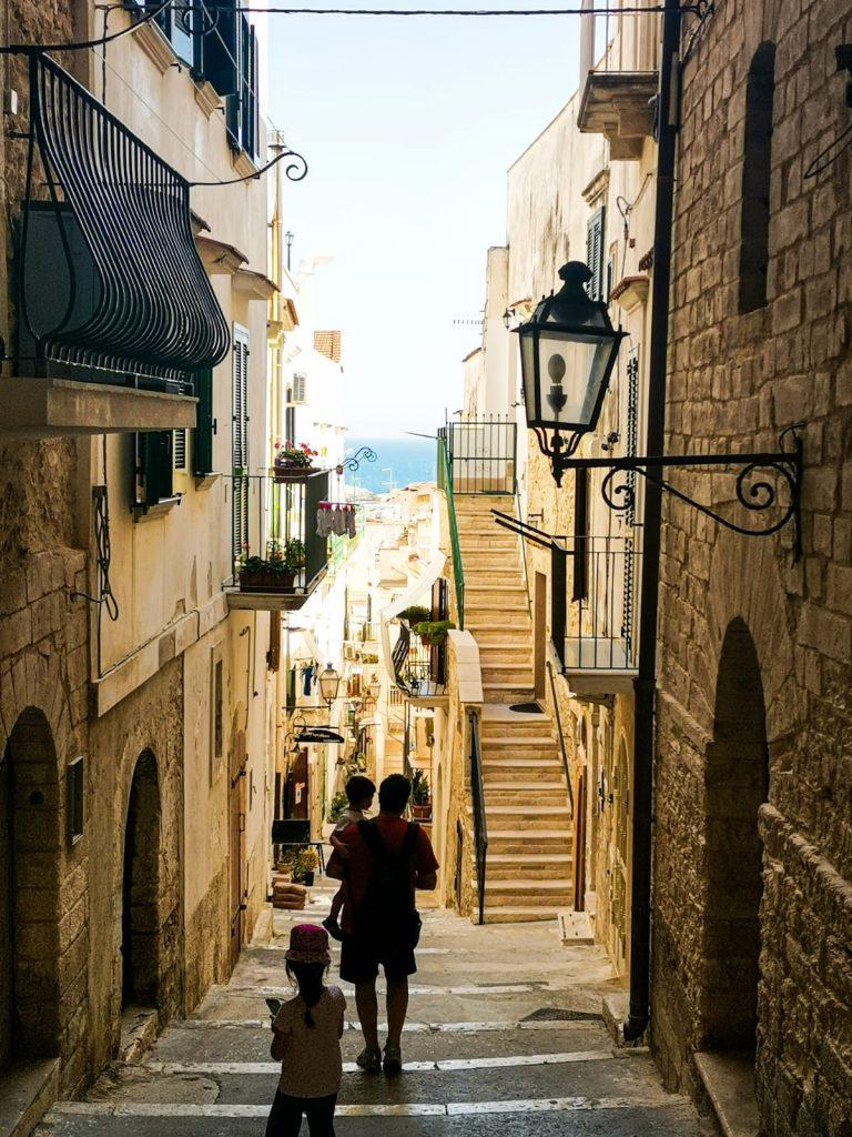 scorcio di Vieste con scalinata: bambini che scendono per le vecchie scale. Un lampione, balconcini, insegne dai piccoli locali sui lati. In fondo, una striscia di mare azzurro