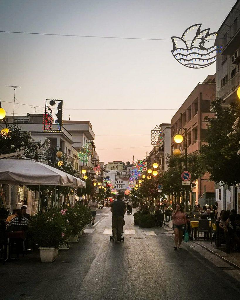 Vieste di sera, corso XIV Novembre con i lampioni accesi. Viale alberato con i tavolini dei bari e delle pizzerie sui marciapiedi e la gente che passeggia. Pezzi sospesi di luminarie accese