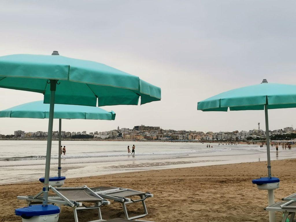 Spiaggia con ombrelloni turchesi aperti sotto un cielo nuvoloso, mare calmo e in lontananza il profilo della città di Vieste che chiude la baia