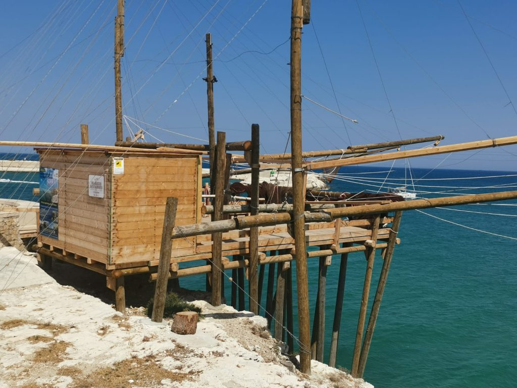 Trabucco sul mare turchese. Casupola di legno come una palafitta con lunghi bracci a cui sono appese le reti per la pesca