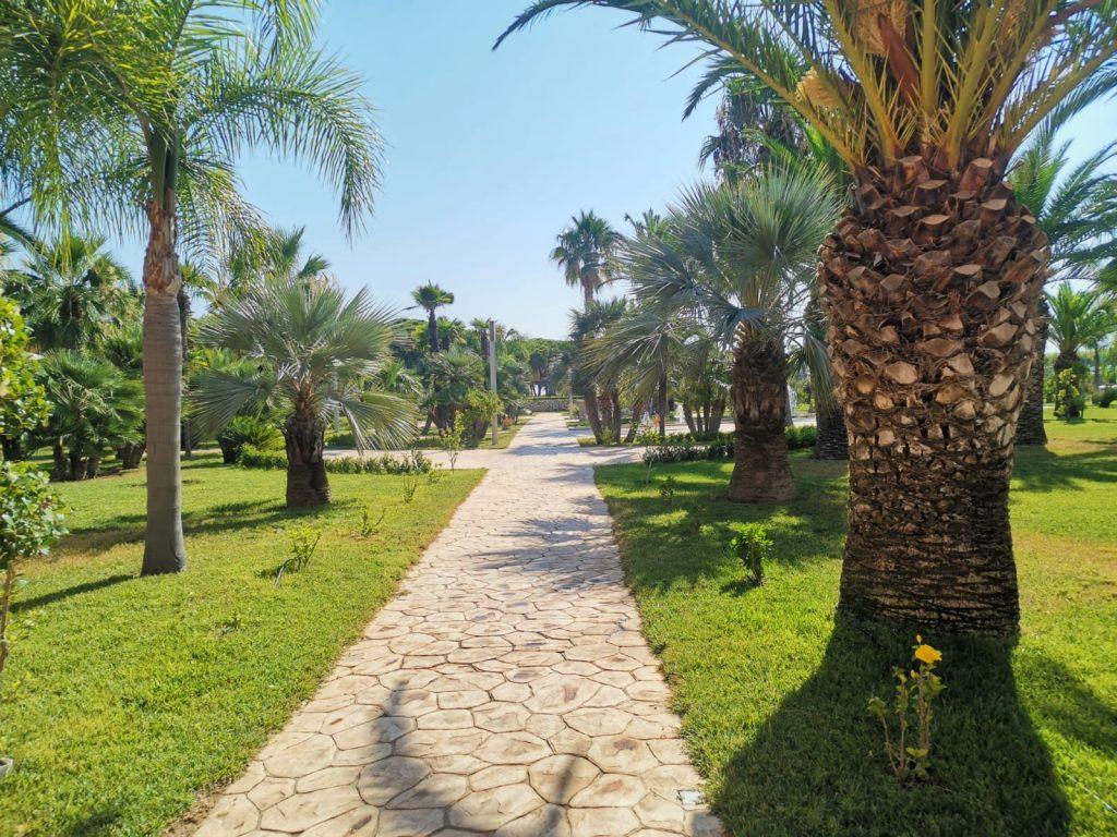 Villaggio Baia Turchese: giardino interno con prato inglese, palme, fontane, sentieri