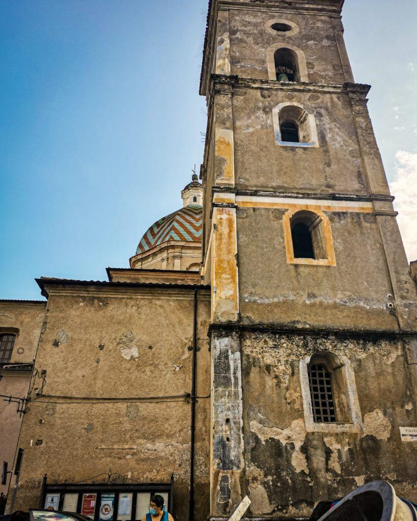 campanile della chiesa madre e cupola maiolicata del corpo centrale. In basso, sulle pareti scrostate, dei manifesti politici