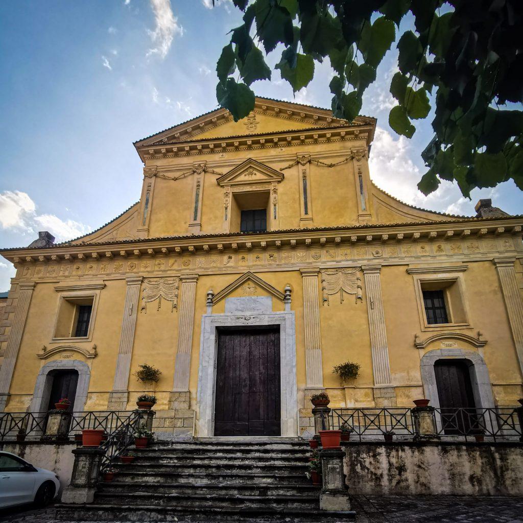 La facciata gialla della chiesa madre di Morano Calabro in stile neo-classico con tre porte che corrispondono alle tre navate interne