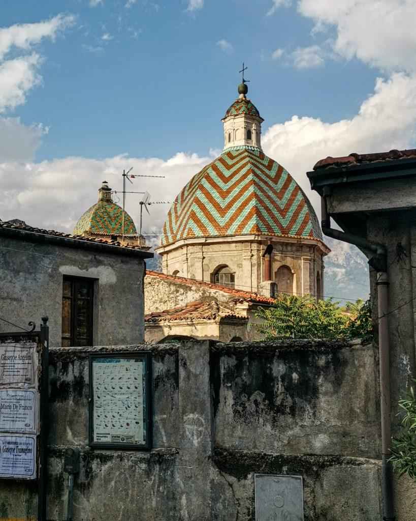 Le cupole maiolicate della chiesa madre spuntano oltre un muro scalcinato, pieno di crepe e vecchi manifesti. La luce esalta le maioliche così come lo sfondo nuvoloso del cielo
