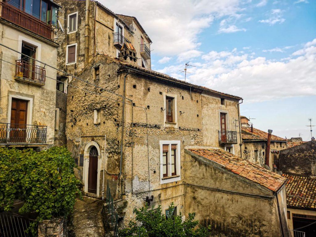 Morano Calabro: casa a strapiombo su più livelli con tetto color ruggine, perfettamente incastrata alle altre case che si trovano ad un livello più basso