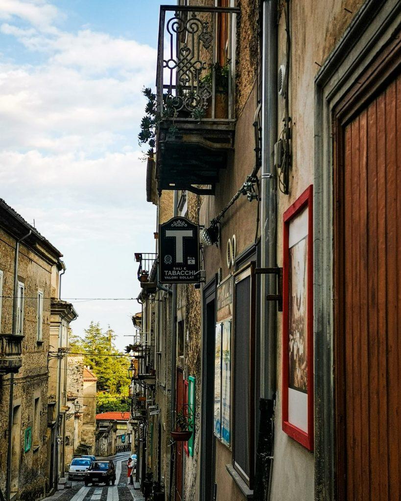Strada con negozietti antichi, insegna di Tabacchi in primo piano, foto d'epoca incorniciate, gli alberi della villa comunale su fondo, balconcini con le ringhiere di ferro battuto